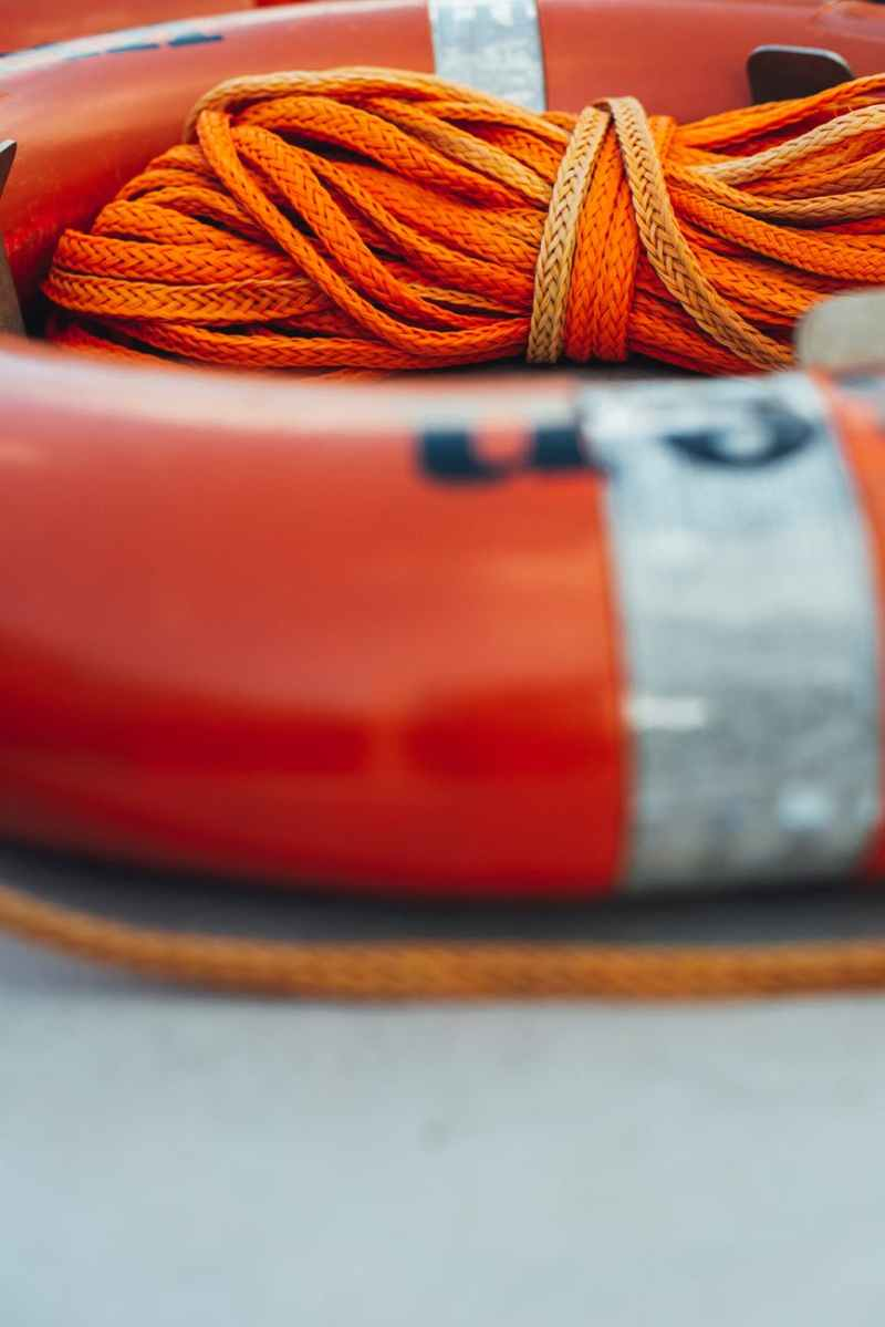 close up photo of orange life ring with orange rope
